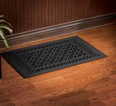 black covers floor vents over laminate wooden floor near small plant in front of wooden