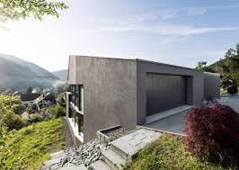 single family house built on a steep slope that leads to the centre of a village
