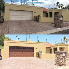 garage door makeover clopay canyon ridge collection faux wood carriage house garage doors add instant warmth and contrast to this beige brick exterior