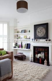 Ornaments on shelving next to fireplace in white living room of  contemporary London home UK