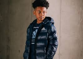 a boyu wearing a navy adidas t shirt with a navy adidas padded coat over