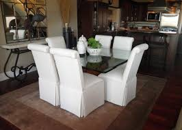 scroll back parsons chairs with kick pleat skirts tucked around a glass dining table