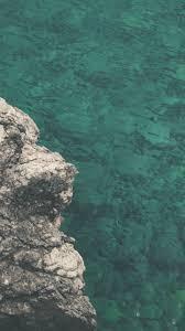 rocks lake body of water sunny day