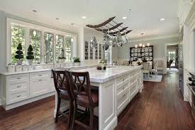 a bright kitchen with white marble countertops and wooden chairs