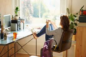 don39t love homeoffice. pensive woman looking through window with feet up on desk in sunny home office don39t love homeoffice 2