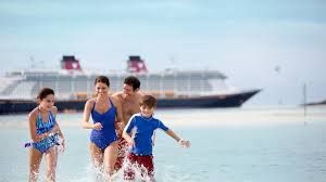 a family of 4 splashes around in shallow waters with a disney cruise line ship in