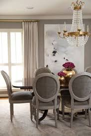 in the dining room painting by saba jawda reupholstered french gray chairs and rug