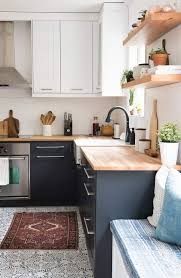 a contrasting graphite grey and white kitchen with light colored butcher block countertops that add coziness
