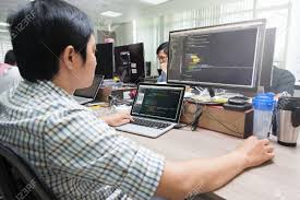 developer office. Asian Outsource Software Developer Looking Screen Sitting At Desk Working Laptop Computer Mobile Application Real Office O
