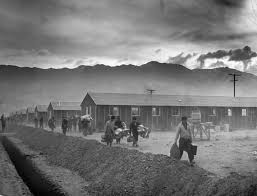 chilling pictures of life at ese internment camps a group of ese americans arrive at the manzanar internment camp carrying their belongings in