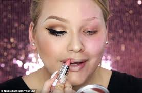 pucker up nikkie adds the finishing touches swiping on both lipstick and gloss