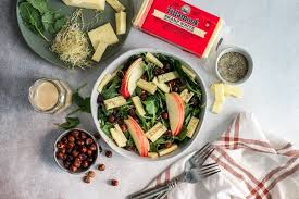 tillamook sharp white cheddar with bowl of apple kale salad and hazelnuts
