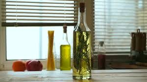 olive oil bottle on kitchen table extra virgin olive oil with rosemary stock