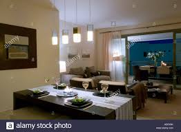 pendant lighting dining room. Pendant Lights Over Dining Table In Modern Apartment Living Room With View Through Open Patio Doors To On Balcony At Night Lighting