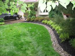 Front yard bed lined with river stone and mulch to create a clean space for  beautifully