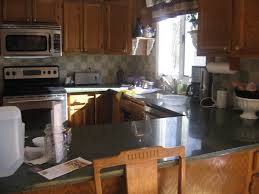 Brown Cabinetry With U Shaped Kitchen Remodel Has Black Granite Countertop  Also Backsplases Gas Stove Oven ...