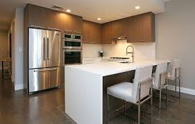 u shaped contemporary kitchen with brown cabinets arctic white countertop and dining peninsula