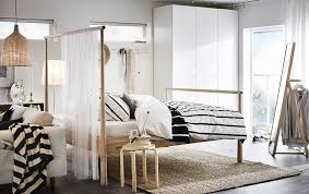 A bedroom furnished with a solid birch bed with a higher end with a sheer  fabric