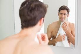 man looking in mirror. rear view of man looking at self in bathroom mirror \u2014 stock photo #36337079