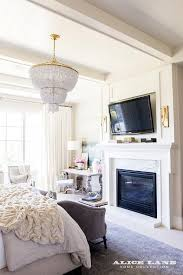 ivory lane exquisitely style bedroom is illuminated by an aerin jacqueline two tier chandelier hung over a gray velvet settee placed on a blue rug in