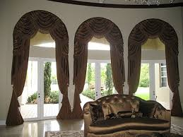 arched window treatments. Arched Top Swags, Fringes And Draperies With Large Tassel Tiebacks Accent This Trio Of Curved Windows Window Treatments