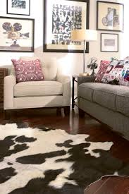 black and white cow skin rug with grey sofa and armchair for living room decoration ideas