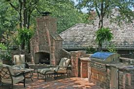 massive colonial design for dark red brick outdoor fireplace with fence and built in grill