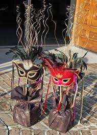 our second centerpiece used bought masquerade masks that ranged from 8 12 each dowel rods were painted with gold glitter spray then secured with