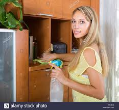 dusting wood furniture. Smiling Woman Dusting Wooden Furniture With Rag And Cleanser At Home Wood