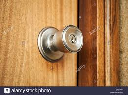 shining metal door handle with keyhole in closed wooden door photo with selective focus and shallow dof