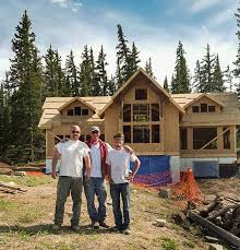 homeowner and two timberbuilt workers standing in front of a diy timber frame house