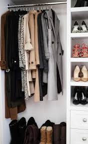 boots sit under winter coats hung from a clothing rail fixed beside built in shoe shelves positioned above a white built in dresser adorning polished nickel