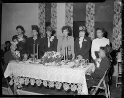 Group portrait of beauty shop owners, from left: Ersley Kincaid, Mary Tims,  Alice Thompson, Carrie Warren Kathleen Holloway, Myrtle Duncan, Ruth  Jenkins, and Rose Johnson, posed around table for tea, at Kay