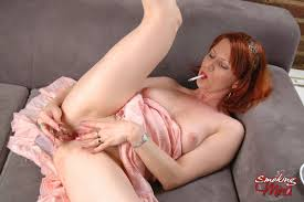 Redhead Smokes A Cigarette And Pleases Her Pink Pussy With Glass.