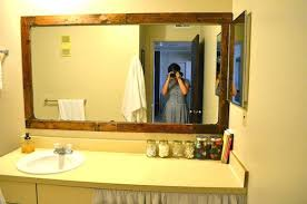 large white wood framed mirrors framing a bathroom mirror with pallets