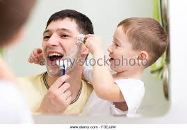 child looking in mirror. child boy and his father shave looking at mirror in bathroom - stock image i