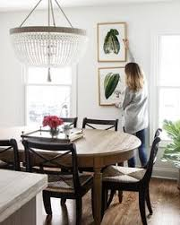 beautiful dining room features a darlana linear pendant illuminating a blond wood dining table lined with a white wingback dining bench for the home