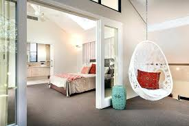 swing chair for bedroom in white with a dark orange throw pillow and seating pad hanging swing chair for bedroom