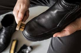 man s hand cleaning elegant leather boots with brush cares about boots beauty and protection from