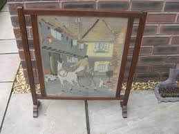a wood frame fire screen with a glazed embroidery of a rider and horses