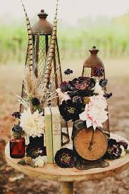 a wedding centerpiece with vine books an antique clock stunning peonies and succulents