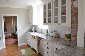 terrific tall white upper kitchen cabinet with white porcelaine backsplash and grey granite countertop also black cup drawers handles