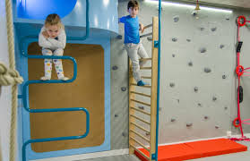 one entire wall of daniel s gym is clad with indoor climbing rocks allowing the kids to climb all the way to the ceiling and across the room