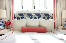 headboard upholstered in manuel canovas calypso fabric on bed dressed in white and red hotel duvet shams red bolster pillows and kelly wearstler