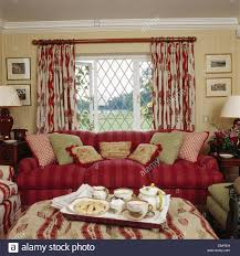 Patterned Curtains For Living Room Tea Tray On Stool In Front Of Red Sofa And Lattice Window With