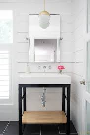 white modern bathroom makeover featuring a steel vanity wall mounted faucet trough sink and
