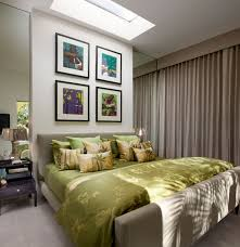 bedroom green bedding set on beige bed and four picture frames on white wall also