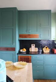 blue green kitchen cabinets with dark wood accents