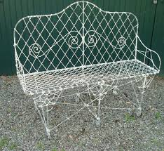 antique wire and wrought iron heavy garden bench with arched back scroll work decoration and curled feet and with remains of old flaking and crusty white