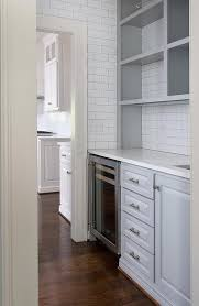 white and grey butler s pantry features walls clad in floor to ceiling white subway tiles accented with gray grout lined with gray cabinets with raised